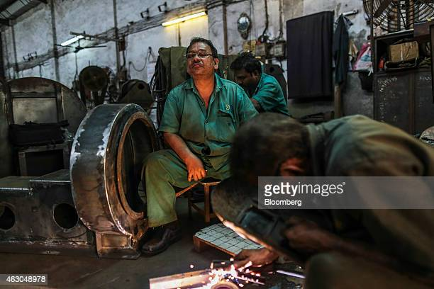 An employee center pauses while working inside an Ishwar Engineering Co factory in Mumbai Maharashtra India on Saturday Feb 7 2015 The International...