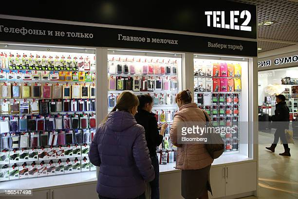 An employee center shows customers mobile phone cases for sale at a Tele2 Russia Holding AB kiosk inside a shopping center in Nizhny Novgorod Russia...