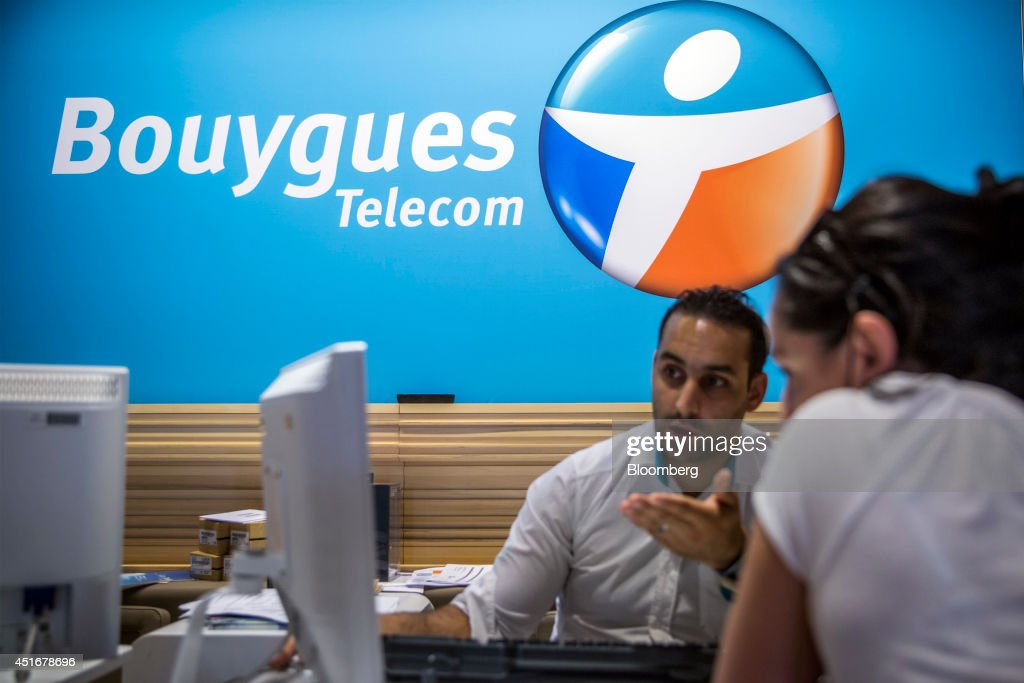 An employee, center, speaks with customer as they sit inside a Bouygues Telecom store, operated by Bouygues SA in Paris, France, on Thursday, July 3, 2014. Bouygues Telecom, France's third-largest mobile operator, was looking for a buyer as profitability and cash generation declined. Photographer: Balint Porneczi/Bloomberg via Getty Images