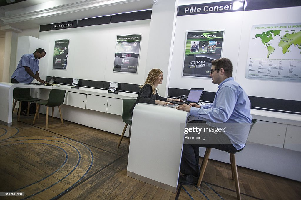 An employee, center, speaks with customer inside a Numericable Group SA cable-television and internet store, operated by Altice SA, in Bordeaux, France, on Friday, July 4, 2014. Altice is raising its stake in Numericable after agreeing in April to merge the French cable provider with Vivendi SA's phone unit SFR, a transaction valued at more than 17 billion euros. Photographer: Balint Porneczi/Bloomberg via Getty Images