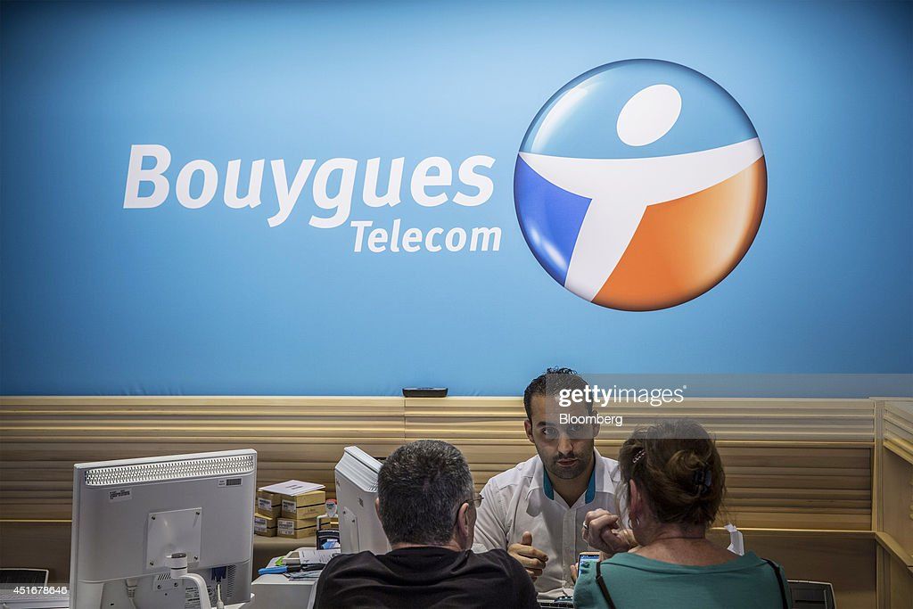 An employee, center, speaks with customers as they sit inside a Bouygues Telecom store, operated by Bouygues SA in Paris, France, on Thursday, July 3, 2014. Bouygues Telecom, France's third-largest mobile operator, was looking for a buyer as profitability and cash generation declined. Photographer: Balint Porneczi/Bloomberg via Getty Images