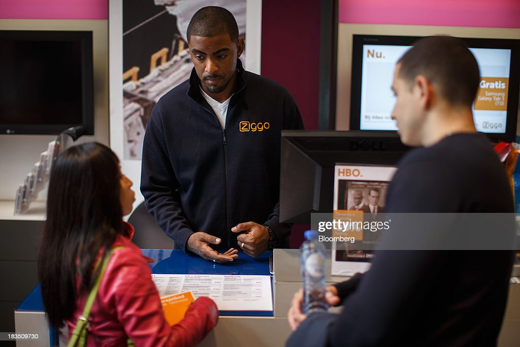 An employee, center, speaks with customers inside a Ziggo NV store in Utrecht, Netherlands, on Friday, Oct. 4, 2013. Cable-TV provider Ziggo, which is 28.5 percent owned by Liberty Global Plc, is pushing into the Dutch mobile market with low-priced packages, following a playbook pioneered by French discount operator Iliad SA. Photographer: Jasper Juinen/Bloomberg via Getty Images