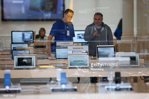 An employee center stands with a customer by a display of MacBook Pro and MacBook Air laptop computers at the Apple Inc store in Amsterdam...