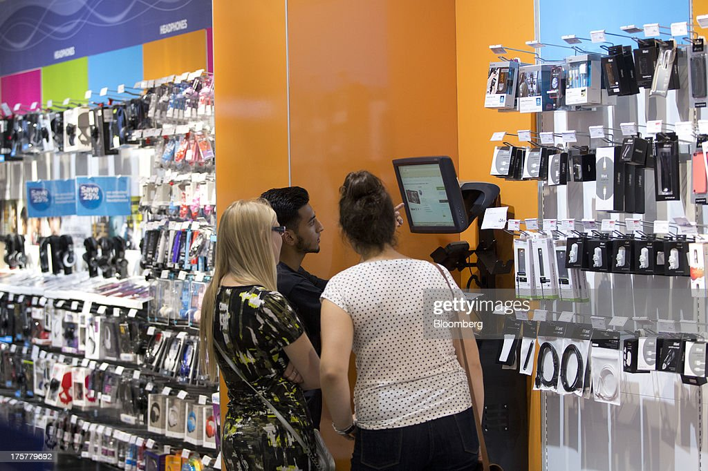 An employee, center, talks with customers about a digital camera, displayed on a screen inside a Currys and PC World 2 in 1 store, operated by Dixons Retail Plc, at the Westfield Stratford City retail complex in London, U.K., on Thursday, Aug. 8, 2013. U.K. consumer confidence rose to the highest in more than three years as Britons' optimism about the economic outlook improved. Photographer: Simon Dawson/Bloomberg via Getty Images