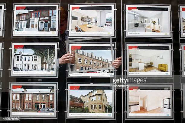 An employee changes a residential property information leaflet displayed in the window of an estate agent in this arranged photograph in the Clapham...