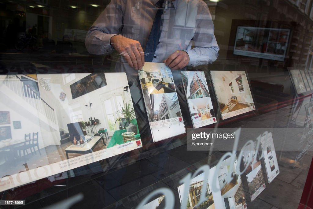 An employee changes an information leaflet for a residential apartment in the window display of an estate agents in London, U.K., on Tuesday, Nov. 12, 2013. Under Bank of England Governor Mark Carney's forward-guidance policy, the central bank has pledged to not to withdraw stimulus at least until unemployment falls to 7 percent. Photographer: Simon Dawson/Bloomberg via Getty Images