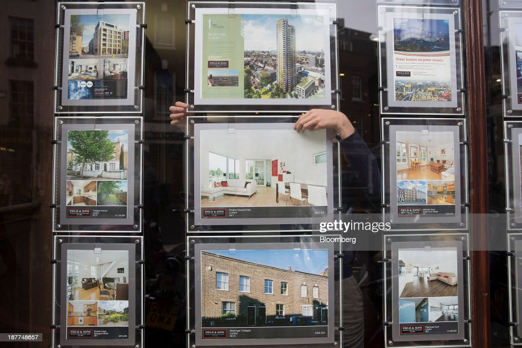 An employee changes an information leaflet for a residential property in the window display of an estate agents in this arranged photograph taken in London, U.K., on Tuesday, Nov. 12, 2013. Under Bank of England Governor Mark Carney's forward-guidance policy, the central bank has pledged to not to withdraw stimulus at least until unemployment falls to 7 percent. Photographer: Simon Dawson/Bloomberg via Getty Images