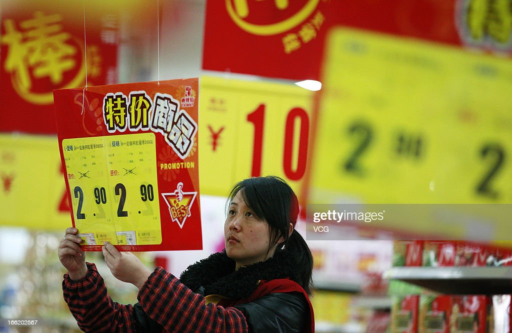 An employee changes posters displaying food prices at a supermarket on April 9, 2013 in Huaibei, China. China's consumer price index (CPI), the main gauge of inflation, rose 2.1 percent year-on-year in March.