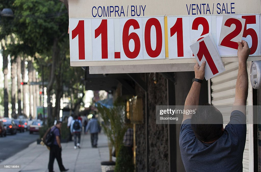 An employee changes the rates on the display board outside the currency exchange center near Avenue Reforma in Mexico City, Mexico, on Tuesday, April 9, 2013. Mexico's peso rose to the strongest since August 2011 after a report showed faster-than-forecast inflation last month, damping speculation that policy makers will cut interest rates to slow the currency's advance. Photographer: Susana Gonzalez/Bloomberg via Getty Images