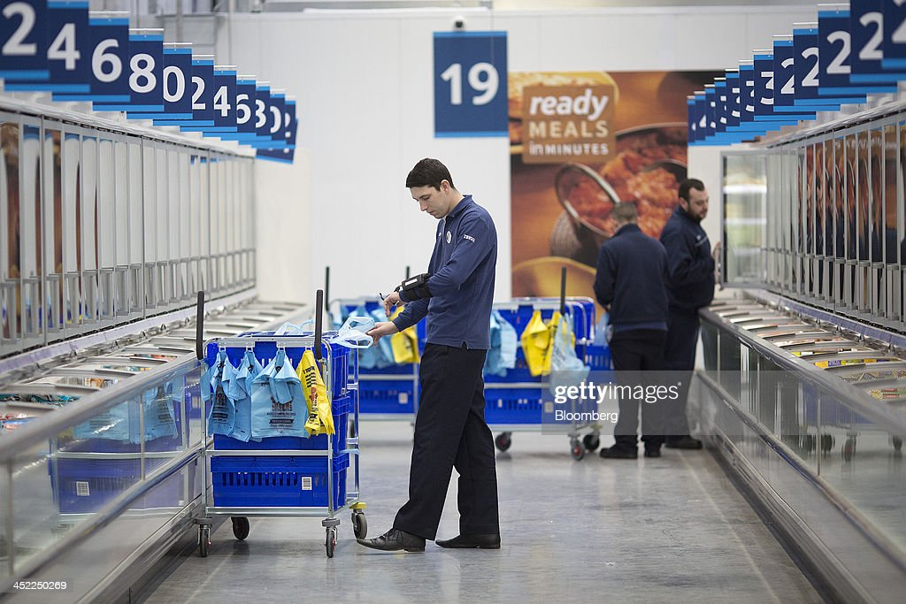 An employee checks a barcode scanner on his wrist as he collects customers frozen food orders at a Tesco Plc on-line distribution center, in Erith, U.K., on Wednesday, Nov. 27, 2013. Tesco Plc, the U.K.'s largest retailer, will sell land near some of its Polish hypermarkets to attract additional services around those stores. Photographer: Simon Dawson/Bloomberg via Getty Images