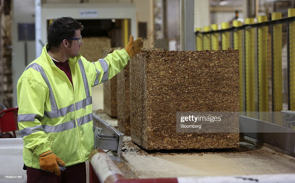 An employee checks a block of raw tobacco as it moves along a conveyor belt ahead of cigarette and tobacco manufacture at Imperial Tobacco Group Plc's factory in Nottingham, U.K., on Friday, Feb. 1, 2013. Imperial Tobacco Group Plc is Europe's second-biggest tobacco company and generates about 40 percent of its profit from the region. Photographer: Chris Ratcliffe/Bloomberg via Getty Images