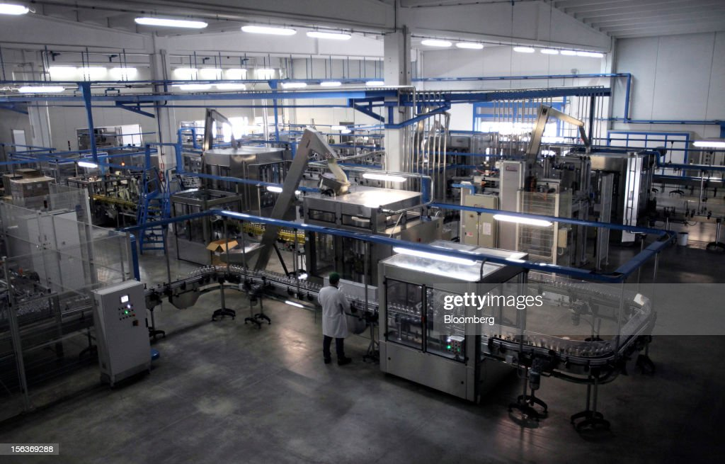 An employee checks a bottle before it is filled with olive on the production line at Industria Olearia Biagio Mataluni Srl's factory in Montesarchio near Benevento, Italy, on Monday, Nov. 12, 2012. Italian olive-oil exports rose 5.7 percent to a record last year, boosted by demand from the U.S. as well as France and Germany, agricultural-markets researcher Ismea said. Photographer: Alessia Pierdomenico/Bloomberg via Getty Images