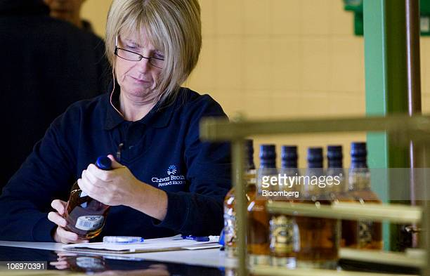 An employee checks a bottle of Chivas Regal whisky at the Pernod Ricard SA bottling plant in Paisley UK on Thursday Nov 18 2010 Pernod Ricard SA the...