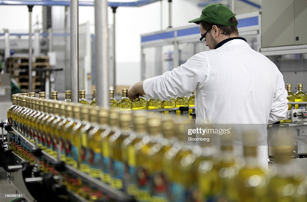 An employee checks a bottle of Dante olive oil as it travels along the production line at Industria Olearia Biagio Mataluni Srl's factory in Montesarchio near Benevento, Italy, on Monday, Nov. 12, 2012. Italian olive-oil exports rose 5.7 percent to a record last year, boosted by demand from the U.S. as well as France and Germany, agricultural-markets researcher Ismea said. Photographer: Alessia Pierdomenico/Bloomberg via Getty Images