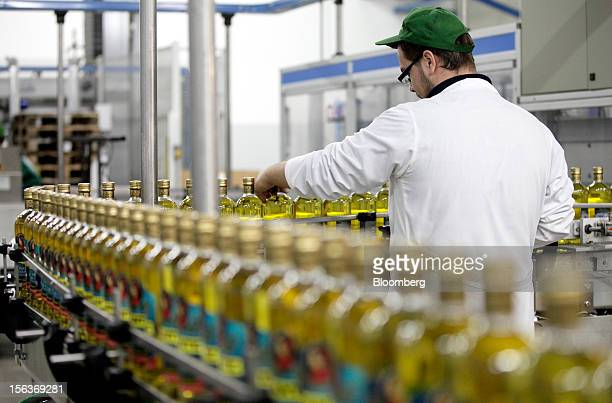 An employee checks a bottle of Dante olive oil as it travels along the production line at Industria Olearia Biagio Mataluni Srl's factory in...
