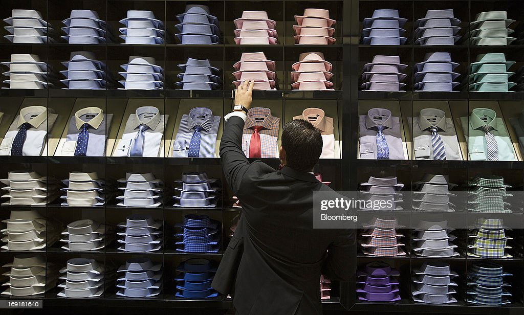 An employee checks a display of mens shirts and ties in this arranged photograph inside Hugo Boss AG's store on Regent Street in London, U.K. on Tuesday, May 21, 2013. Hugo Boss AG reiterated its earnings forecast for the year after the German luxury-clothing maker said its retail business increased sales by 14 percent in the first quarter as it opened more outlets. Photographer: Simon Dawson/Bloomberg via Getty Images