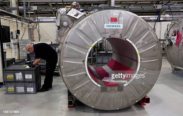 An employee checks a goods stock list near a magnet manufactured for use in Magnetic Resonance Imaging scanners at the Siemens AG Magnet Technology...