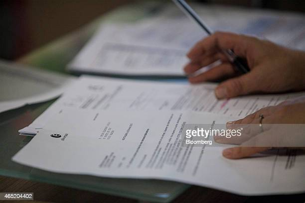 An employee checks a jobseeker's documents inside a Pole Emploi job center the French national employment agency in Montauban France on Tuesday March...