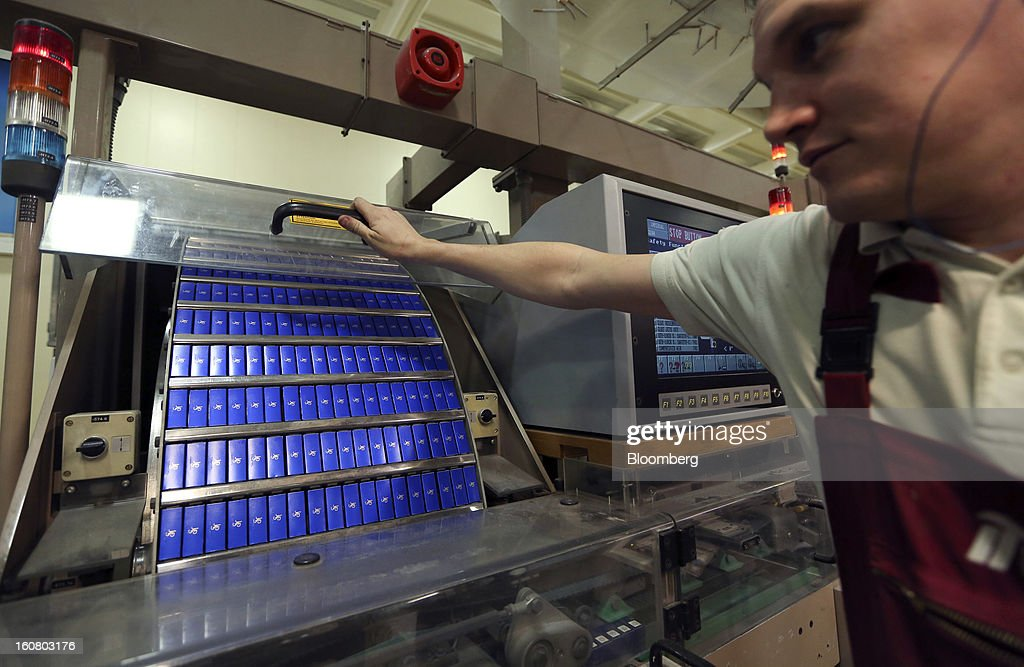 An employee checks a machine as filled packets of John Player Special (JPS) cigarettes, manufactured by Imperial Tobacco Group Plc, pass through it on the production line at the company's factory in Nottingham, U.K., on Friday, Feb. 1, 2013. Imperial Tobacco Group Plc is Europe's second-biggest tobacco company and generates about 40 percent of its profit from the region. Photographer: Chris Ratcliffe/Bloomberg via Getty Images