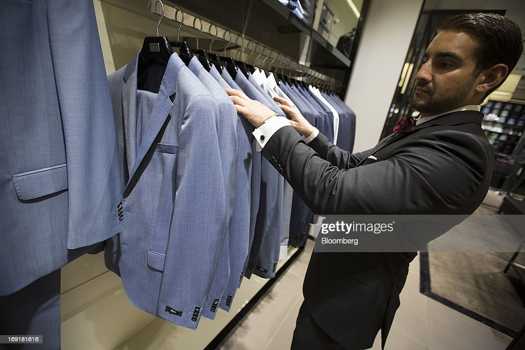 An employee checks a rail of mens suits in this arranged photograph inside Hugo Boss AG's store on Regent Street in London, U.K. on Tuesday, May 21, 2013. Hugo Boss AG reiterated its earnings forecast for the year after the German luxury-clothing maker said its retail business increased sales by 14 percent in the first quarter as it opened more outlets. Photographer: Simon Dawson/Bloomberg via Getty Images