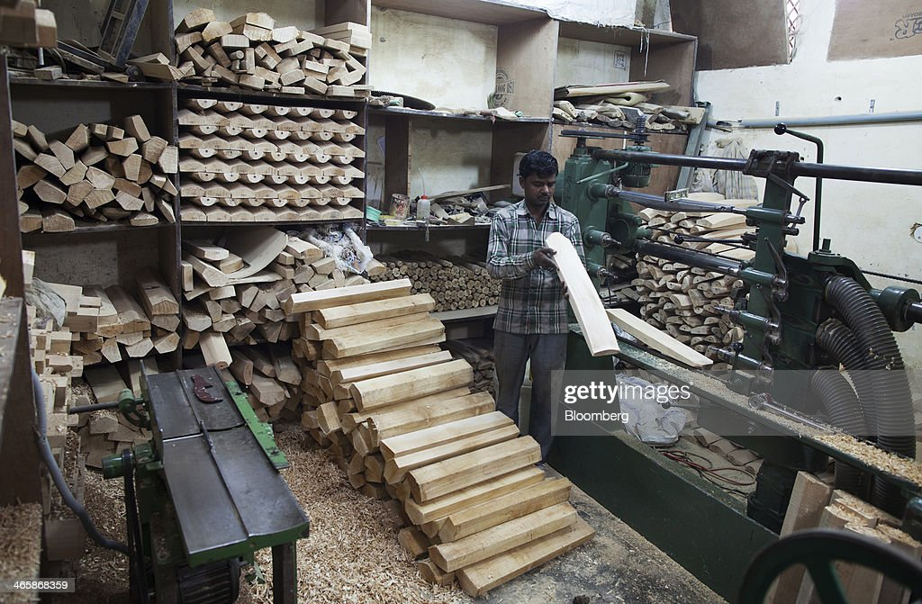 An employee checks a sample as he works on a multiple bat cutting machine at a Stanford Cricket Industries factory in Meerut, Uttar Pradesh, India, on Wednesday, Jan. 29, 2014. The Indian Premier League (IPL), the worlds richest cricket competition, auction for IPL 2014 is scheduled to begin on Feb. 12 with the seasons first match to be played on April 8. Photographer: Prashanth Vishwanathan/Bloomberg via Getty Images