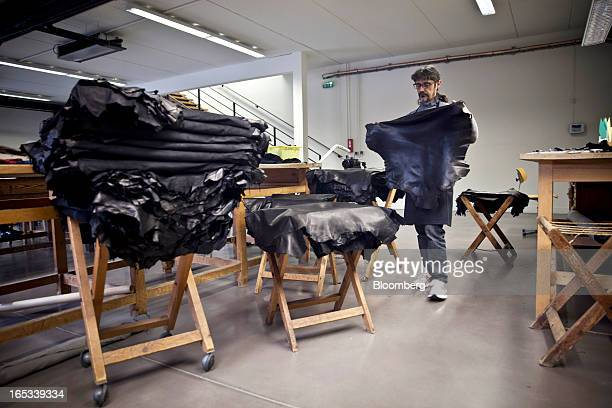 An employee checks a section of leather hide used during the manufacture of handmade luxury gloves at the Causse Gantier factory in Millau France on...