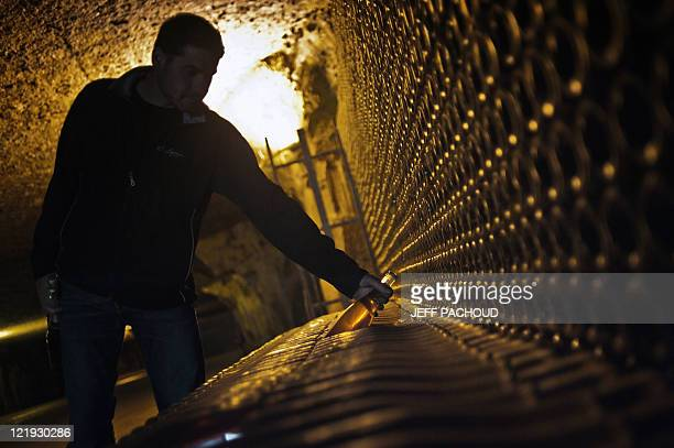 An employee checks bottles of AOC 'Crémant de Bourgogne' wine at the Bailly Lapierre cellars on August 19 2011 in the French central city of...