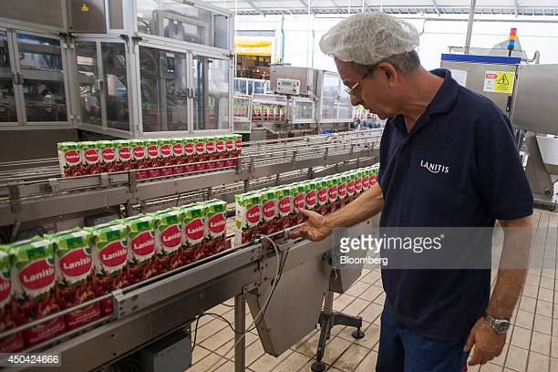 An employee checks cartons of Lantis fruit juice as they travel along the production line at the Lanitis Bros Ltd bottling plant part of the CocaCola...