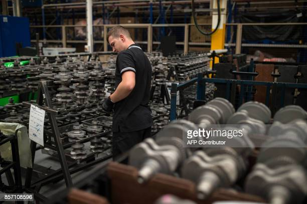 An employee checks components at the Triumph Motorcycles factory in Hinckley central England on October 2 2017 Triumph which was originally formed as...