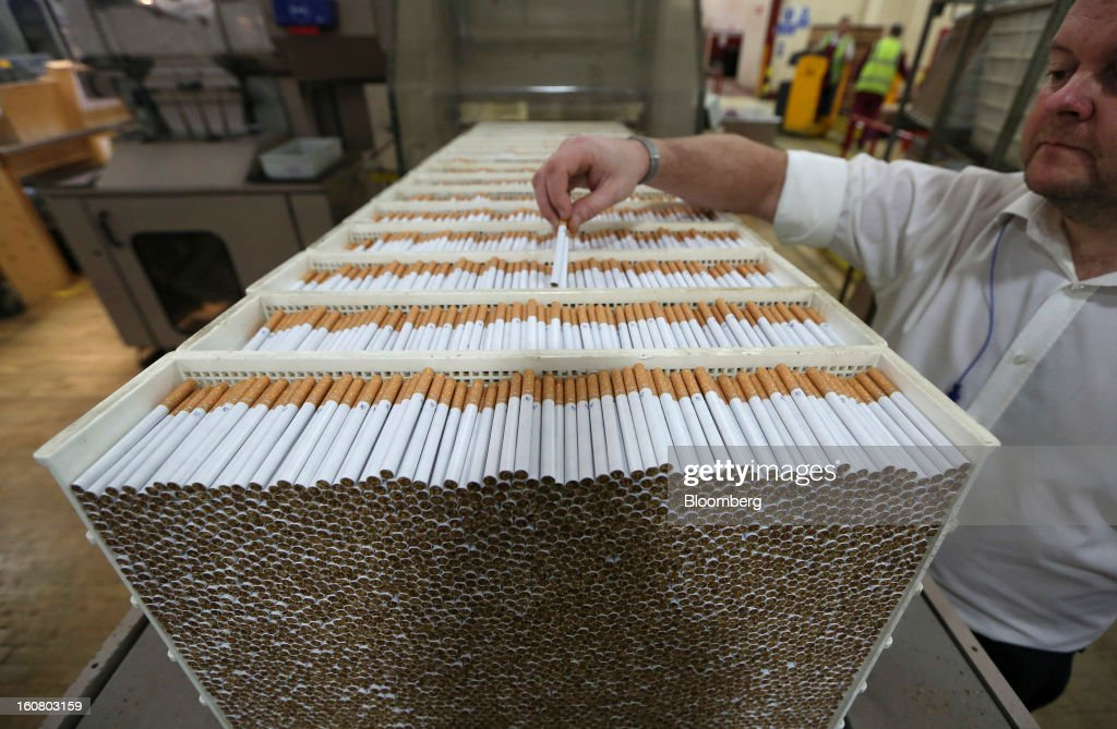 An employee checks finished John Player Special (JPS) cigarettes, manufactured by Imperial Tobacco Group Plc, at the company's factory in Nottingham, U.K., on Friday, Feb. 1, 2013. Imperial Tobacco Group Plc is Europe's second-biggest tobacco company and generates about 40 percent of its profit from the region. Photographer: Chris Ratcliffe/Bloomberg via Getty Images