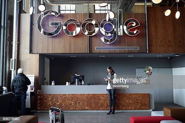 An employee checks her mobile device in the lobby of Google Canada's engineering headquarters in Waterloo Ontario Canada on Friday Jan 22 2016 The...