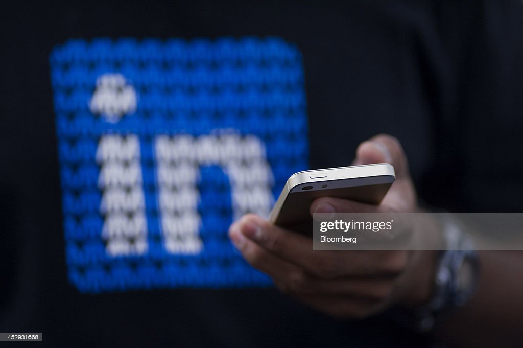 An employee checks his Apple Inc. iPhone while working at LinkedIn Corp. headquarters in Mountain View, California, U.S., on Monday, July 28, 2014. LinkedIn Corp. is scheduled to release earnings figures on July 31. Photographer: David Paul Morris/Bloomberg via Getty Images