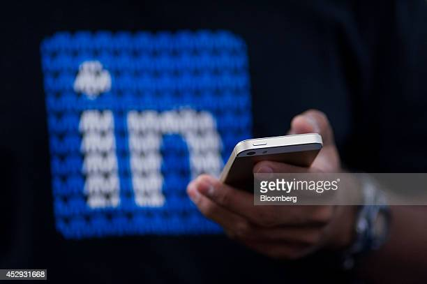 An employee checks his Apple Inc iPhone while working at LinkedIn Corp headquarters in Mountain View California US on Monday July 28 2014 LinkedIn...