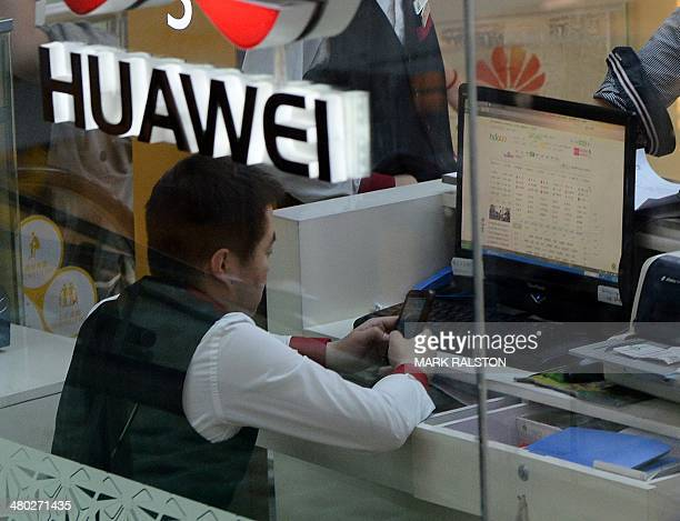 An employee checks his phone at a Huawei store in Beijing on March 24 2014 Chinese telecoms and Internet giant Huawei condemned the US National...