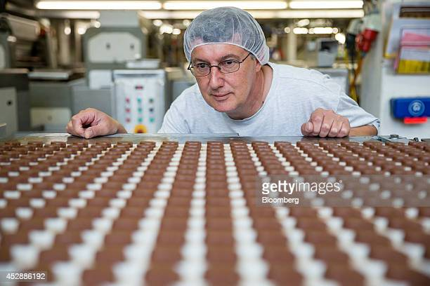 An employee checks Lindt chocolates for defects on the production line inside the Lindt Spruengli AG factory in Kilchberg Switzerland on Tuesday July...