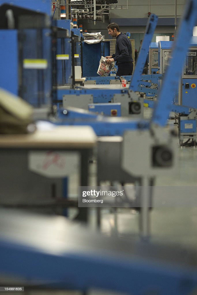 An employee checks newspapers after printing at the El Pais printing plant in Madrid, Spain, on Tuesday, Oct. 30, 2012. Prisa, the publisher of El Pais newspaper, has announced staff reductions and salary cuts. Photographer: Angel Navarrete/Bloomberg via Getty Images