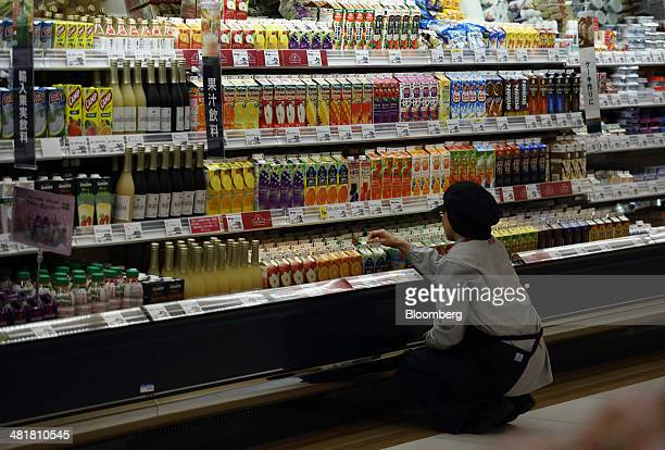 An employee checks packaged drinks at an Aeon Co supermarket in Chiba Japan on Tuesday April 1 2014 Japan's economy will probably withstand a sales...
