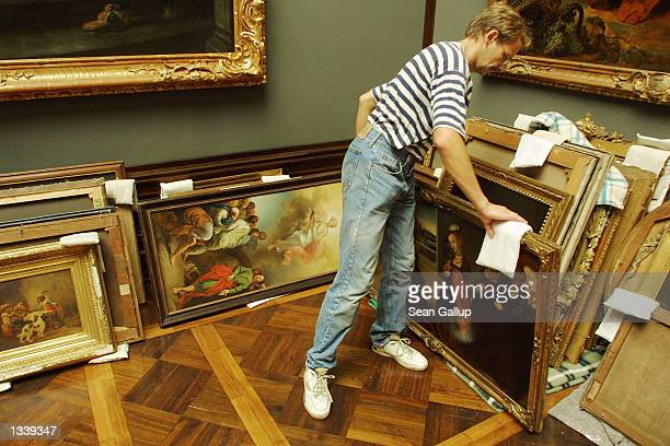 An employee checks paintings that had been saved from rising floodwaters at the Zwinger museum in Dresden Germany August 17 2002 Earlier firefighters...