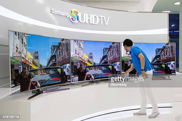 An employee checks Samsung Electronics Co SUHD 4K televisions on display at the company's Galaxy Zone showroom in Seoul South Korea on Monday July 6...
