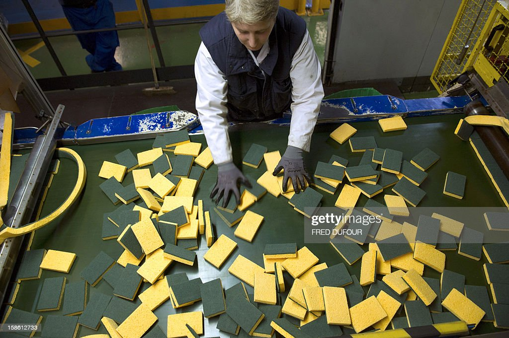 An employee checks sponges at the factory of French sponge brand Spontex on December 19, 2012 in Beauvais. AFP PHOTO / FRED DUFOUR