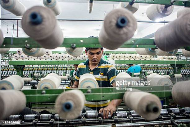 An employee checks spools of dehaired pashmina is processed into threads at the spinning unit of the Valley Wool Ltd factory in Srinagar Jammu and...