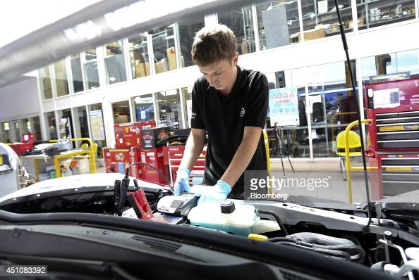 An employee checks the battery in the engine compartment of a new Nissan Juke automobile produced by Nissan Motor Co during a predelivery check for a...