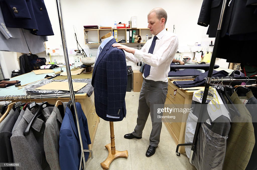 An employee checks the details on a finished suit jacket in the workshop of the tailors Dege & Skinner based on Savile Row in London, U.K., on Tuesday, July 2, 2013. New orders at manufacturers rose for a fourth month in June, led by the textiles clothing industry, while input costs fell for a third month. Photographer: Chris Ratcliffe/Bloomberg via Getty Images