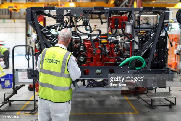 An employee checks the engine section of an Enviro 400 bus under construction at the Alexander Dennis Ltd factory in Guildford UK on Monday Sept 11...
