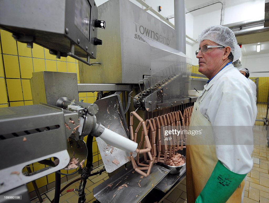 An employee checks the production of sausage links in a sausage processing line of Charles Christ, a French firm specialized in canned cooked dishes and condiments, on January 11, 2013 at Connerre, western France.