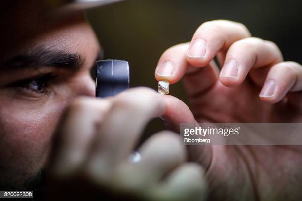 An employee checks the quality of a rough diamond at the MSD polishing laboratory in the diamond district of Antwerp Belgium on Thursday July 20 2017...