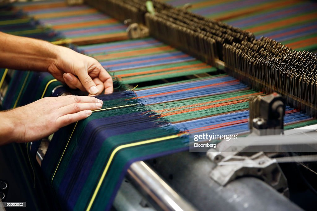 An employee checks the threads on a weaving machine during tartan material production at Lochcarron John Buchan Ltd.'s plant in Selkirk, U.K., on Tuesday, Aug. 12, 2014. Scottish nationalists seeking independence from the U.K. lost ground in the latest poll of voting intentions for the Sept. 18 referendum, as campaigners to keep the 307-year-old U.K. intact extended their lead. Photographer: Simon Dawson/Bloomberg via Getty Images