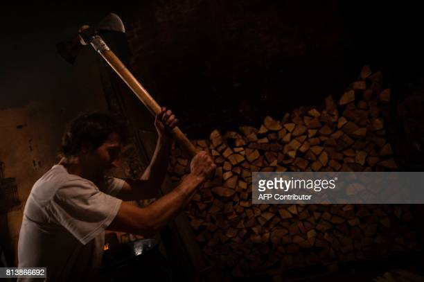 An employee chops wood to feed the fire for the cooking of 'churros' at the traditional churreria 'La Manueta' on July 13 in Pamplona northern Spain...
