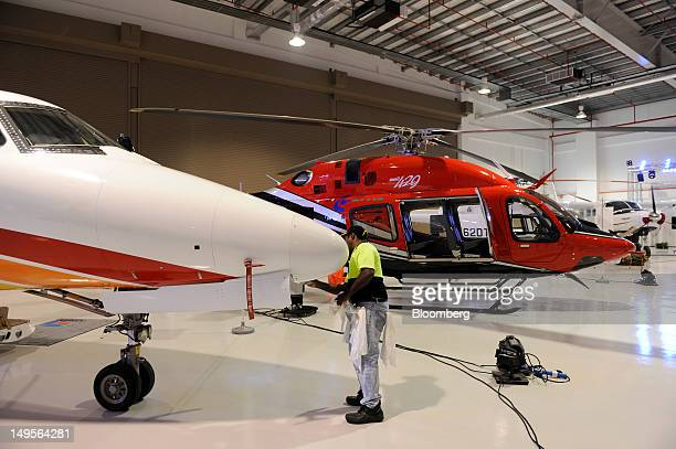 An employee cleans a Cessna Aircraft Co aircraft in the hangar of the Bell Helicopter and Cessna service center in Singapore on Tuesday July 31 2012...