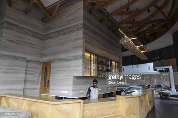An employee cleans a counter inside a cafeteria at The World Towers a luxury residential project developed by Lodha Developers Ltd in Mumbai India on...